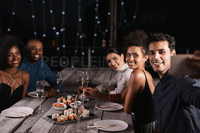 Buy stock photo Shot of a group of friends taking a selfie while out for dinner
