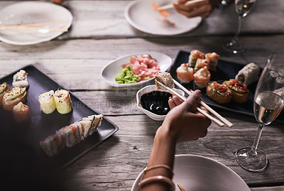 Buy stock photo Cropped shot of an unrecognizable person eating sushi at a restaurant