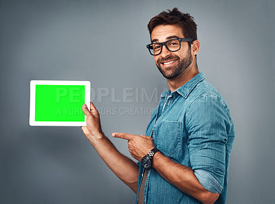 Buy stock photo Studio shot of a handsome young man showing a digital tablet with a green screen against a grey background