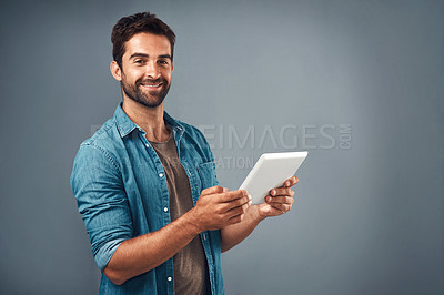 Buy stock photo Studio shot of a handsome young man using a digital tablet against a grey background