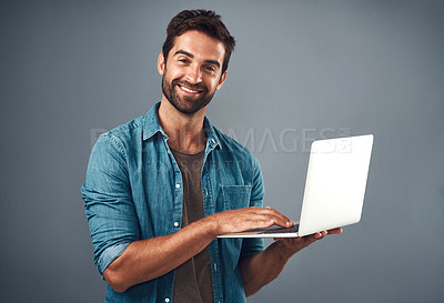 Buy stock photo Studio shot of a handsome young man using a laptop against a grey background