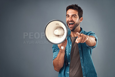 Buy stock photo Studio shot of a handsome young man using a megaphone against a grey background