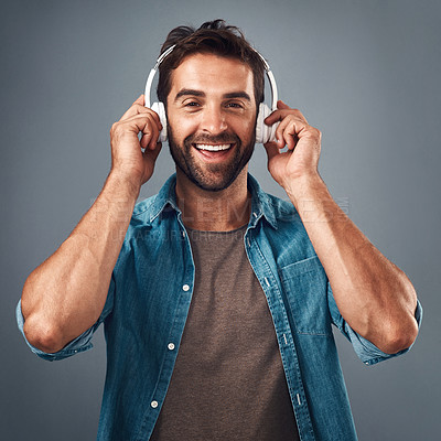 Buy stock photo Studio shot of a handsome young man wearing headphones against a grey background
