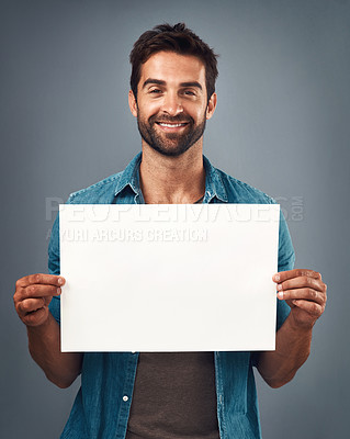 Buy stock photo Studio shot of a handsome young man holding a blank placard against a grey background
