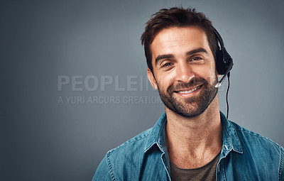 Buy stock photo Studio portrait of a handsome young man wearing a headset against a grey background