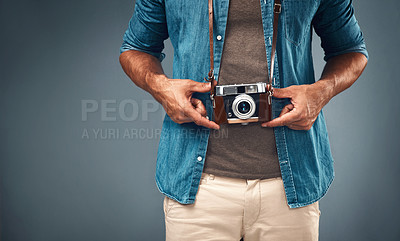 Buy stock photo Cropped studio shot of a young man with a camera around his neck against a grey background