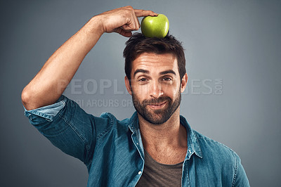 Buy stock photo Studio shot of a handsome young man balancing an apple on his head against a grey background