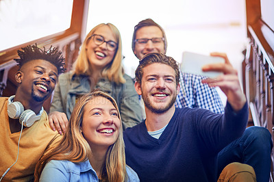 Buy stock photo Cropped shot of a group of diverse university students taking a selfie on the staircase on campus