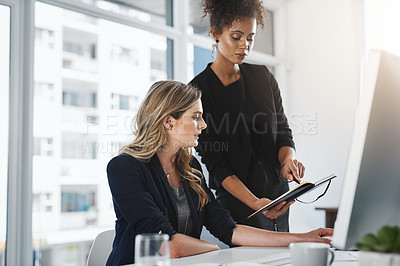 Buy stock photo Shot of two businesswomen working together in an office