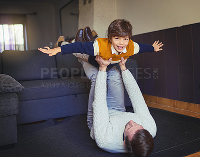 Buy stock photo Shot of a man lifting his son into mid-air