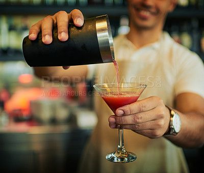 Buy stock photo Shot of an unrecognizable barman pouring a drink in a fancy glass inside of a restaurant during the day