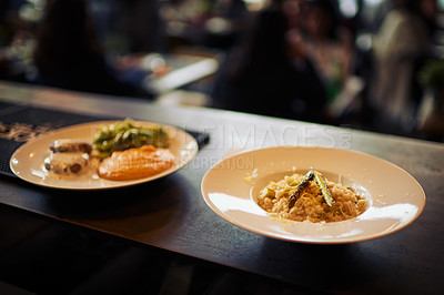 Buy stock photo Shot of two plates of food standing on a counter and ready to be taken out to customers inside of a restaurant during the day