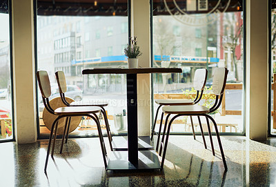 Buy stock photo Shot of an empty table with chairs inside of a restaurant during the day