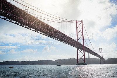 Buy stock photo Low angle shot of a massive bridge over the ocean with clouds in the background outside during the day
