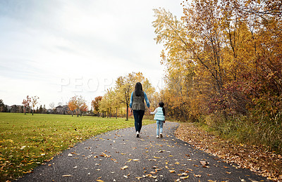 Buy stock photo Rearview shot of a mother and her little daughter enjoying a walk outdoors