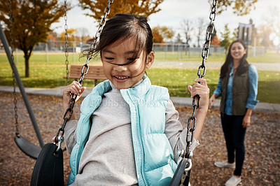 Buy stock photo Shot of a little girl playing on a swing at the park with her mother in the background