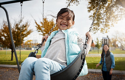Buy stock photo Portrait of a little girl playing on a swing at the park with her mother in the background