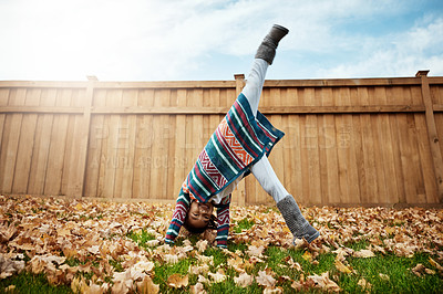 Buy stock photo Shot of an adorable little girl doing cartwheels an autumn day outdoors