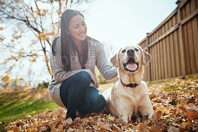 Buy stock photo Shot of an attractive young woman having fun with her dog on an autumn day in a garden