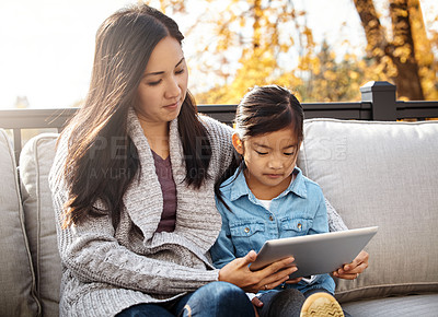 Buy stock photo Shot of an adorable little girl using a digital tablet with her mother on an autumn day outdoors