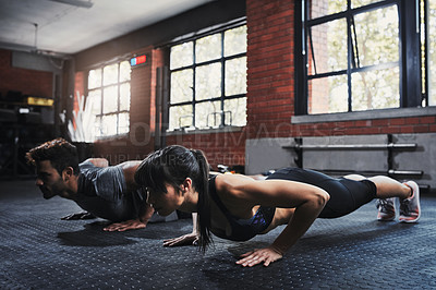 Buy stock photo Shot of two young people working out at the gym