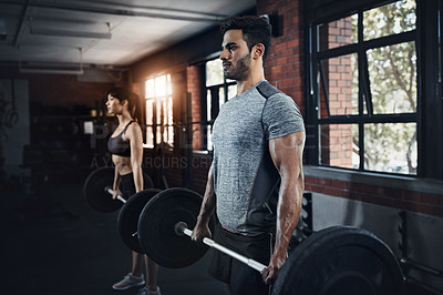 Buy stock photo Shot of a young man and woman working out with weights at the gym