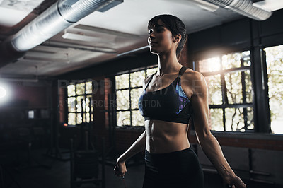 Buy stock photo Shot of a beautiful young woman jumping rope as part of her exercise routine