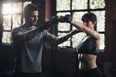 Buy stock photo Cropped shot of a young man and woman working out at the gym