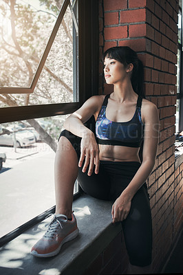 Buy stock photo Shot of a beautiful young woman sitting at the gym
