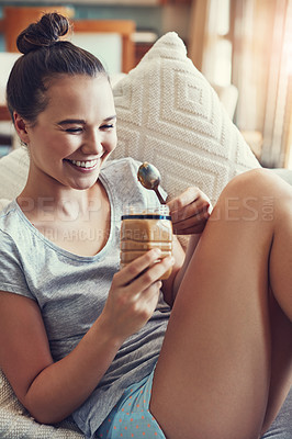 Buy stock photo Shot of an attractive young woman eating peanut butter while relaxing on the sofa at home