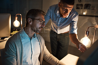 Buy stock photo Shot of two businesspeople working late on a computer in an office