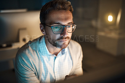 Buy stock photo Shot of a mature businessman working late on a computer in an office