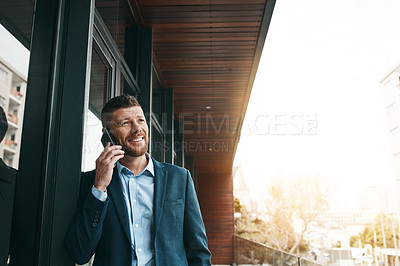 Buy stock photo Shot of a mature businessman talking on a cellphone on the office balcony