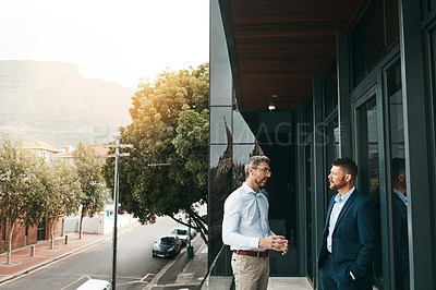 Buy stock photo Shot of two businessmen having a discussion on the office balcony