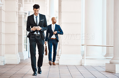 Buy stock photo Shot of a young handsome businessman using a cellphone outside