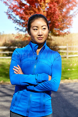 Buy stock photo Shot of a sporty young woman standing outdoors