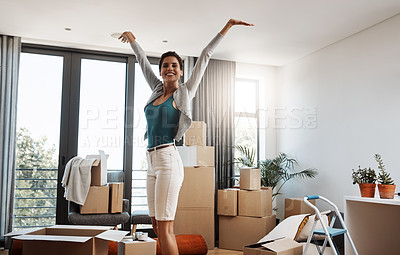 Buy stock photo Cropped portrait of an attractive young woman standing with her arms outstretched while moving into a new house
