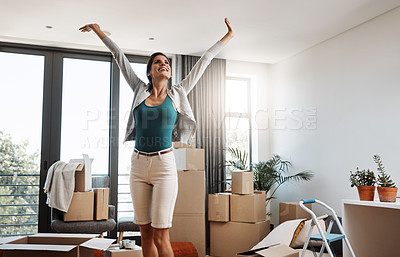 Buy stock photo Cropped shot of an attractive young woman standing with her arms outstretched while moving into a new house