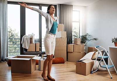 Buy stock photo Full length shot of an attractive young woman standing with her arms outstretched while moving into a new house