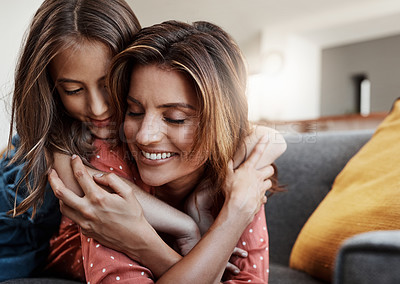 Buy stock photo Cropped shot of an attractive young woman and her daughter hugging while spending time together at home