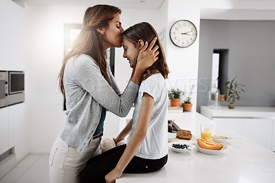 Buy stock photo Cropped shot of an attractive young woman kissing her daughter on the forehead while spending time together at home