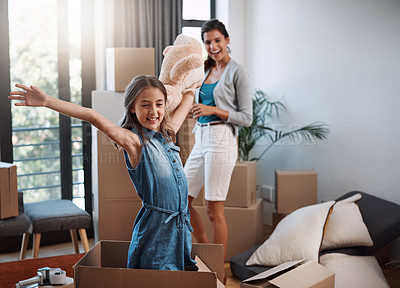 Buy stock photo Cropped shot of an attractive young woman and her daughter moving into a new house