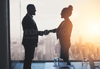Buy stock photo Silhouetted shot of two businesspeople shaking hands in an office