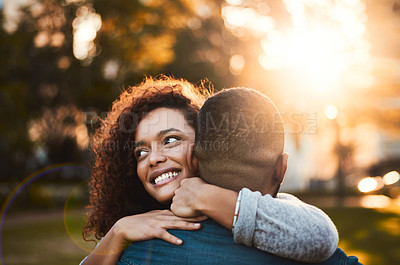 Buy stock photo Shot of a young woman hugging her boyfriend outdoors
