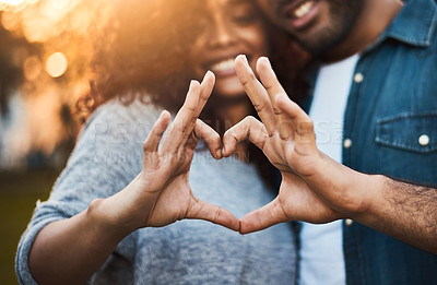 Buy stock photo Shot of a a young couple making a heart shape with their fingers outdoors