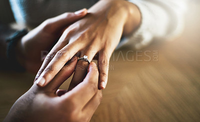 Buy stock photo Cropped shot of a man putting an engagement ring onto his girlfriend's finger