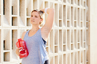 Buy stock photo Cropped shot of an attractive young woman taking a break while working out in the city
