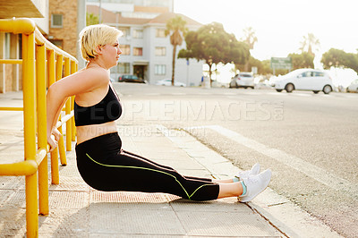 Buy stock photo Shot of an attractive young woman working out in the city