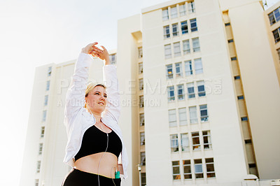 Buy stock photo Cropped shot of an attractive young woman working out in the city