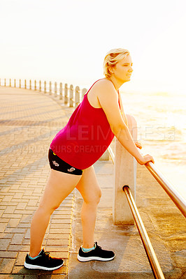 Buy stock photo Shot of an attractive young woman working out on the promenade